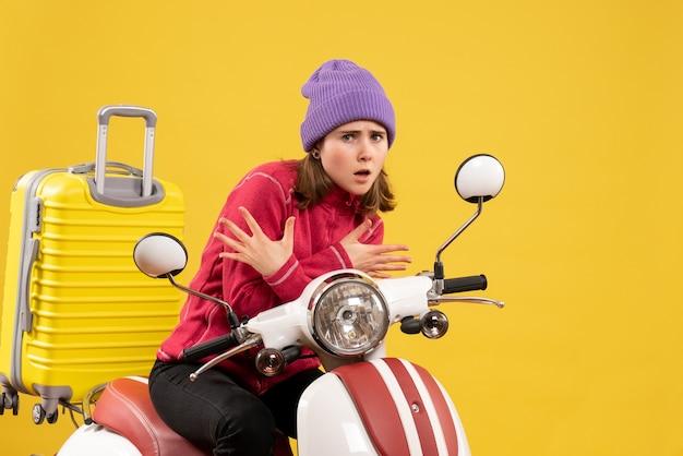 Vooraanzicht doodsbang jong meisje in paarse hoed op bromfiets