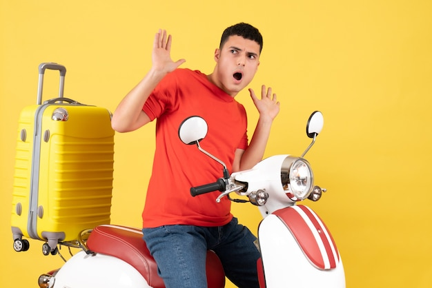 Vooraanzicht doodsbang jonge man in vrijetijdskleding op bromfiets met gele koffer