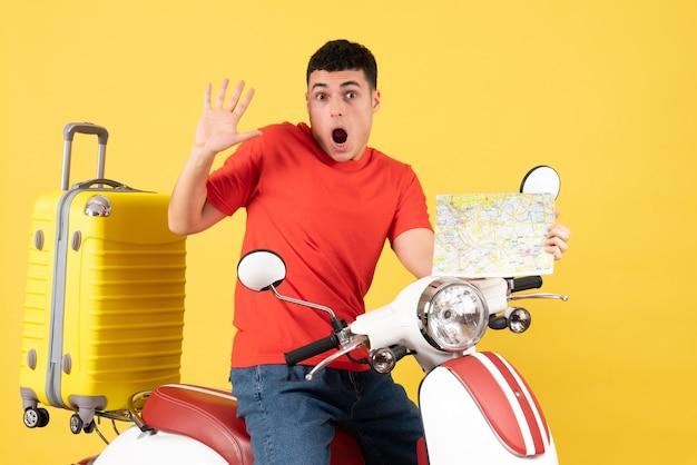 Vooraanzicht doodsbang reismens in vrijetijdskleding op bromfiets met reiskaart