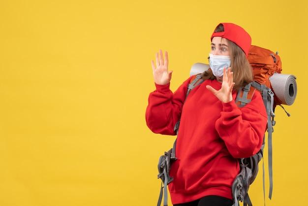 Vooraanzicht doodsbang vrouwelijke toerist met rugzak en masker