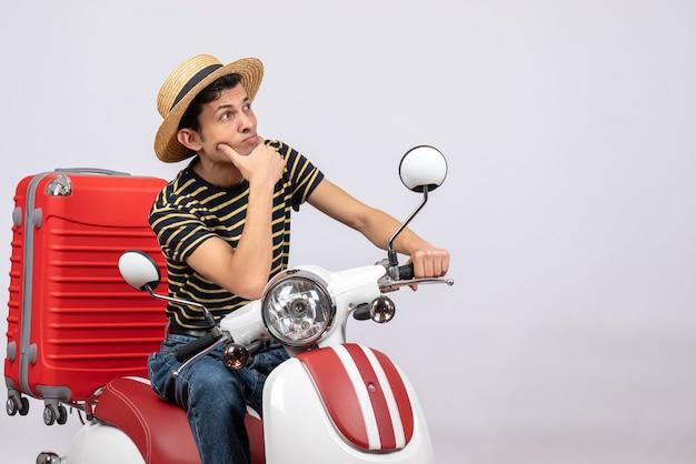 Vooraanzicht doordachte jonge man met strooien hoed op bromfiets