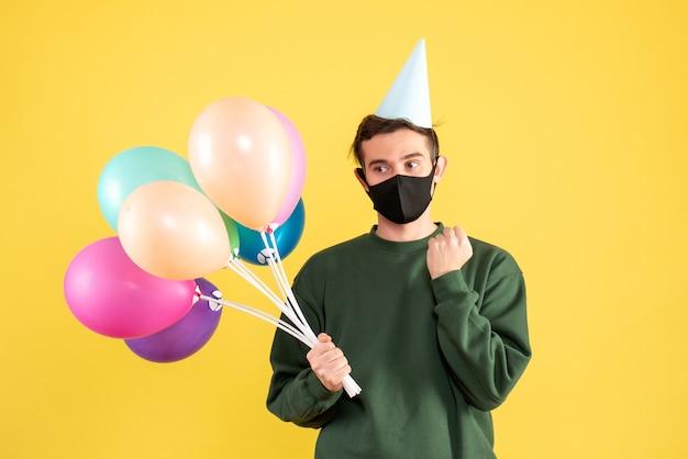 Vooraanzicht doordachte jongeman met feestmuts en kleurrijke ballonnen staande op geel