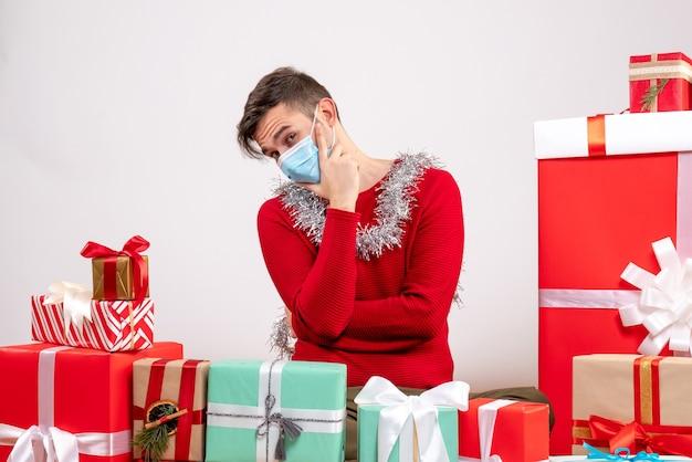 Vooraanzicht doordachte jongeman met masker wijzend op rug rond xmas geschenken zitten