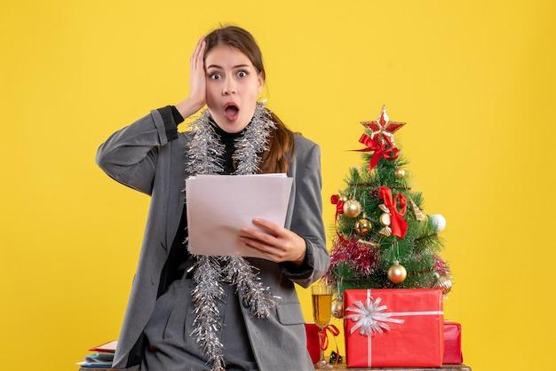 Vooraanzicht doordachte meisje met documenten met haar hoofd in de buurt van kerstboom en geschenken cocktail