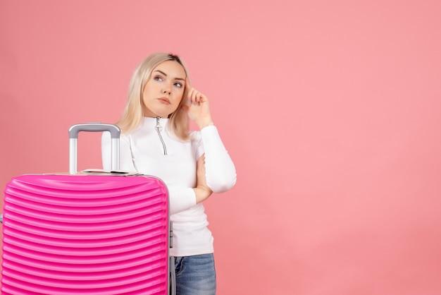 Vooraanzicht doordachte mooie vrouw met roze koffer