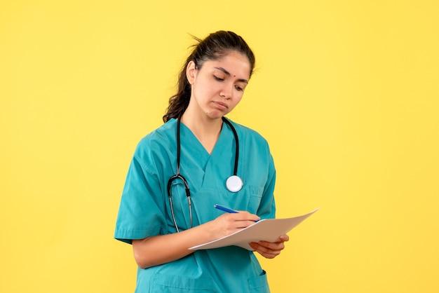 Vooraanzicht doordachte vrij vrouwelijke arts die iets op papier op gele achtergrond schrijft