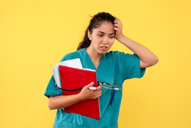 Vooraanzicht doordachte vrouwelijke arts met de mappen van de stethoscoopholding in haar hand die zich op gele achtergrond bevindt