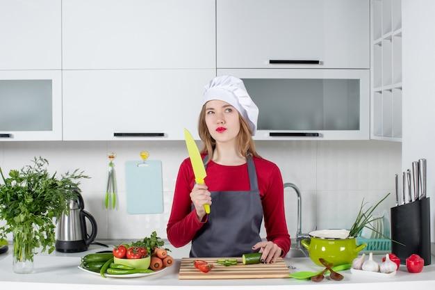 Vooraanzicht doordachte vrouwelijke kok in schort met mes