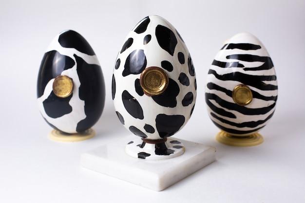 Vooraanzicht drie chocolade-eieren zwart en wit in de kleur van een koe zebra en dolmatijnen op stand