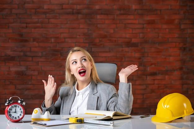 Vooraanzicht dromende vrouwelijke ingenieur achter haar werkplek