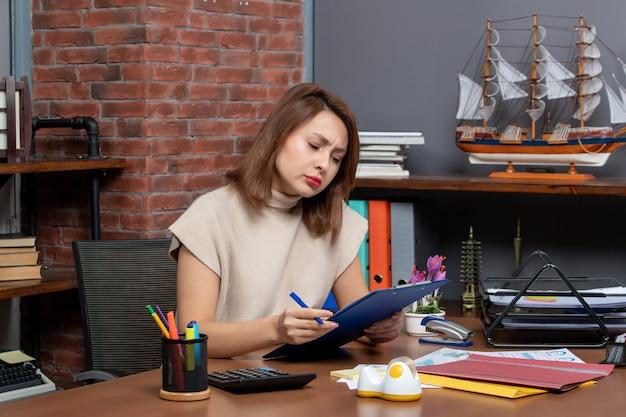 Vooraanzicht drukke zakenvrouw die documenten controleert die aan het bureau op kantoor zitten