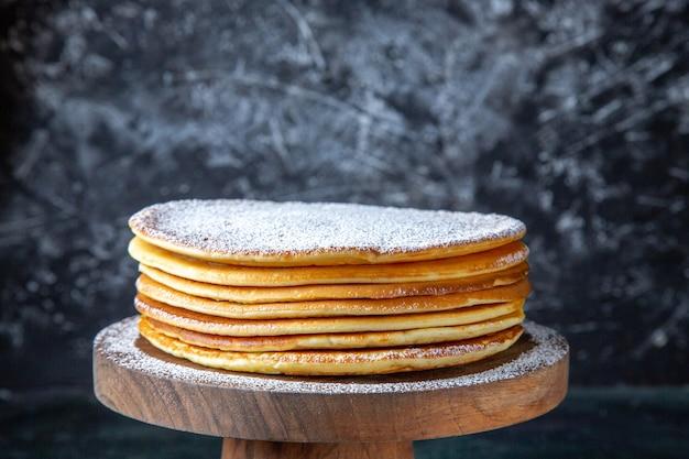 Vooraanzicht dunne cakevellen met suikerpoeder op ronde houten plank donkere ondergrond