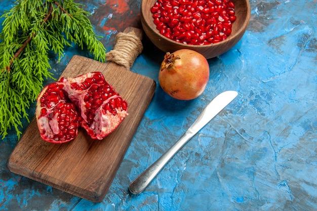 Vooraanzicht een gesneden granaatappel en diner mes op snijplank granaatappel zaden in kom en granaatappel op blauwe achtergrond vrije ruimte