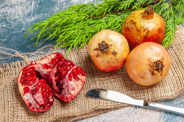 Vooraanzicht een gesneden granaatappel granaatappels diner mes op blauw-witte achtergrond