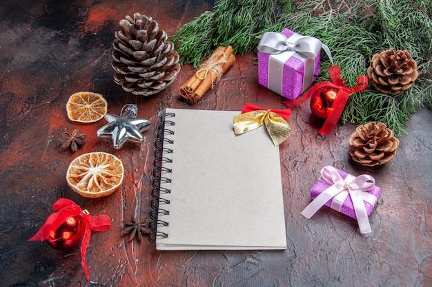 Vooraanzicht een notitieboekje met kleine boog dennenboom takken kegels kerstboom speelgoed en geschenken kaneel steranijs op donkerrode achtergrond