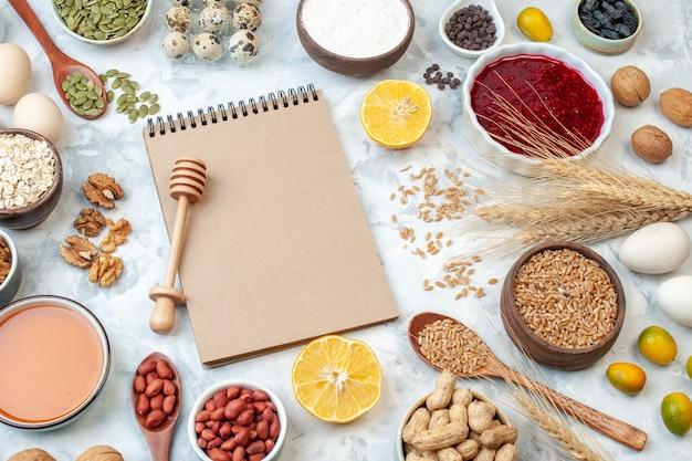 Vooraanzicht eenvoudig notitieblok met eieren meel gelei verschillende noten en zaden op witte achtergrond noot kleur cake zoete taart foto suiker deeg fruit