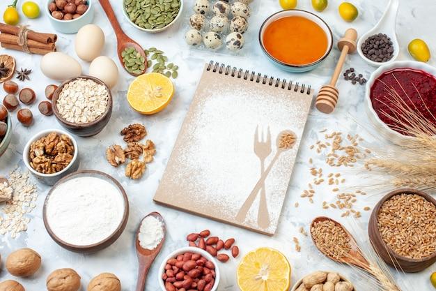 Vooraanzicht eenvoudige blocnote met eieren meel gelei en verschillende noten op witte achtergrond noot suiker kleur taart foto fruit zoete cake deeg