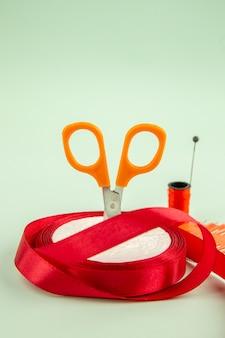 Vooraanzicht eenvoudige naalden met een schaar en rode strik op groene achtergrond