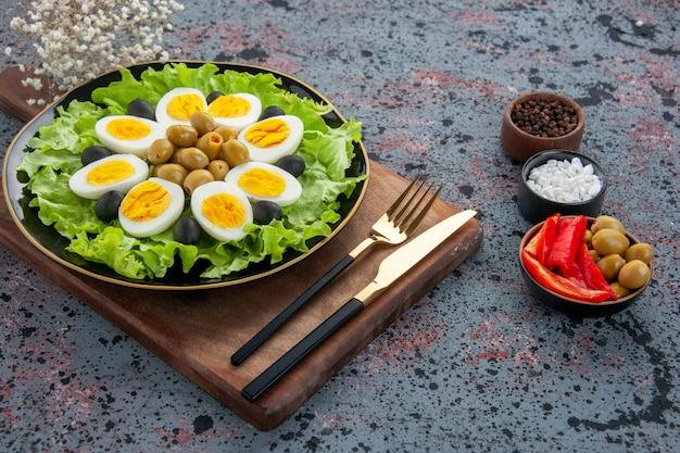 Vooraanzicht eiersalade groene salade en olijven met tomaten op lichte achtergrond