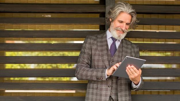 Vooraanzicht elegante volwassen mannelijke browsen tablet Premium Foto