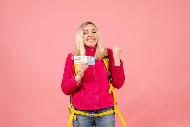 Vooraanzicht erg opgewonden reizigersvrouw in vrijetijdskleding die het kaartje van de rugzakholding draagt
