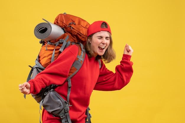 Vooraanzicht erg opgewonden vrouwelijke reiziger met rugzak die haar gevoelens uitdrukt