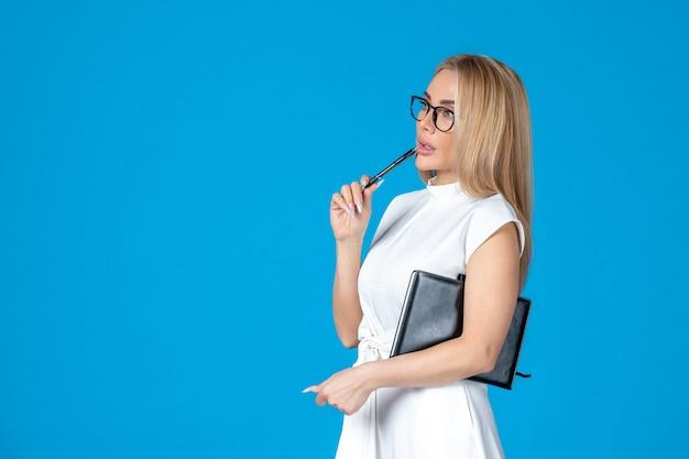 Vooraanzicht femaleer in witte jurk poseren met notitieblok op blauw werk