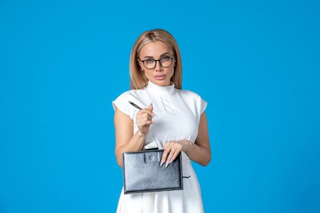 Vooraanzicht femaleer in witte jurk poseren met notitieblok op blauwe werkautoriteit