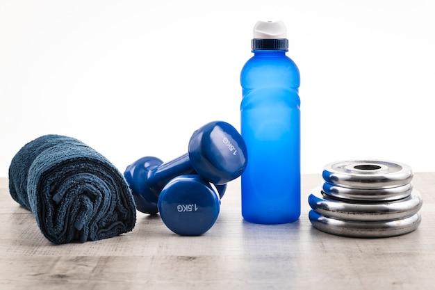 Vooraanzicht fitnessapparatuur met water en handdoek naast
