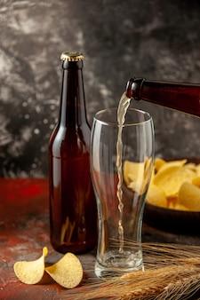 Vooraanzicht fles beer die in het glas stroomt met cips op de donkere achtergrond