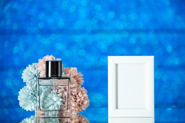 Vooraanzicht fles parfum kleine witte fotolijst bloemen op blauwe wazige achtergrond met vrije ruimte