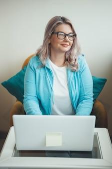 Vooraanzicht foto van een senior blonde vrouw die lacht tijdens het werken op de laptop