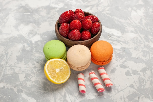 Vooraanzicht franse macarons met verse aardbeien op wit oppervlak fruit bessen cake koekje zoete suiker