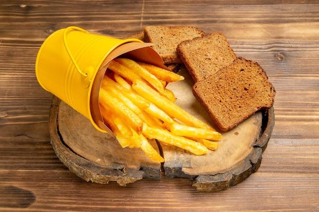 Vooraanzicht frietjes met donkere broden op bruin bureau aardappel fastfood maaltijdbrood