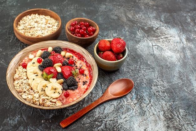 Vooraanzicht fruitige muesli met gesneden fruit op licht-donkere tafel gezondheid granen fruit