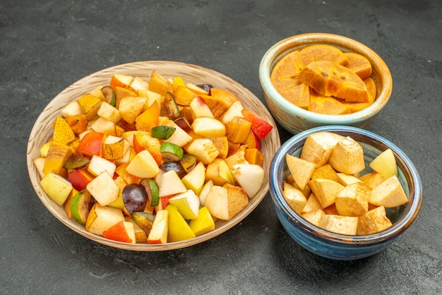 Vooraanzicht fruitige salade met vers gesneden fruit op grijs vers fruit van de lijstboom