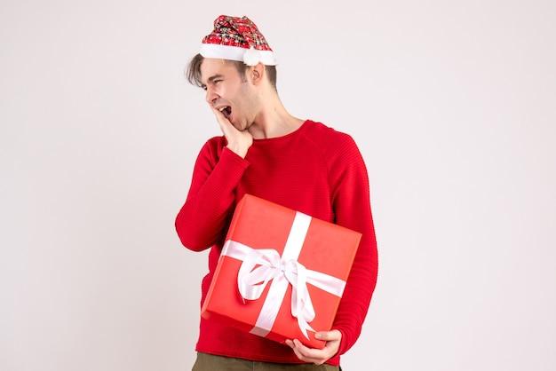 Vooraanzicht gapende jonge man met kerstmuts staande op een witte achtergrond