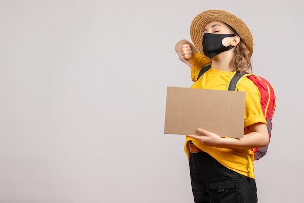 Vooraanzicht gapende vrouwelijke reiziger met rugzak met karton