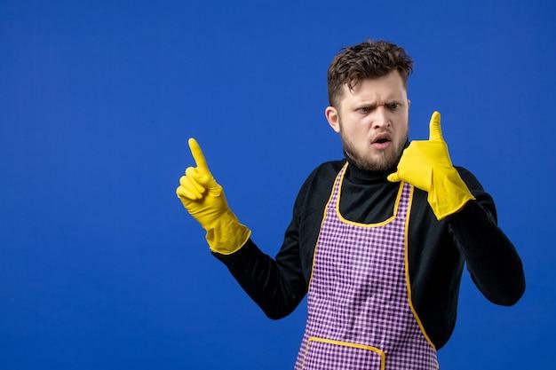 Vooraanzicht geagiteerde mannelijke huishoudster in zwarte trui die naar de hand kijkt op blauwe geïsoleerde ruimte