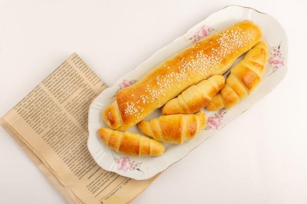 Vooraanzicht gebak en croissants bruin lekker gekookt in witte glazen plaat op de witte vloer