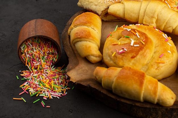 Vooraanzicht gebak samen met croissants op het bruine bureau samen met kleurrijke snoepjes in het donker