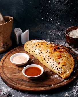 Vooraanzicht gebak samen met witte en rode sauzen op de bruine houten ronde bureau en grijze oppervlak