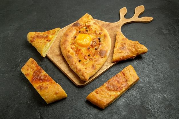 Vooraanzicht gebakken eierbrood heerlijk deegbroodje op de donkere ruimte