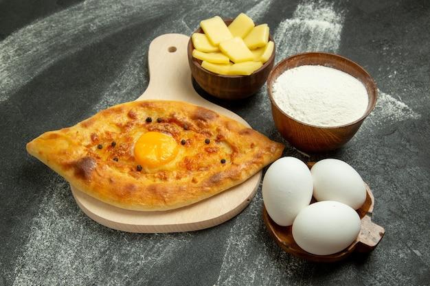 Vooraanzicht gebakken eierbrood heerlijk deegbroodje op het donkere bureau