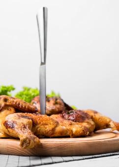 Vooraanzicht gebakken hele kip op snijplank met mes