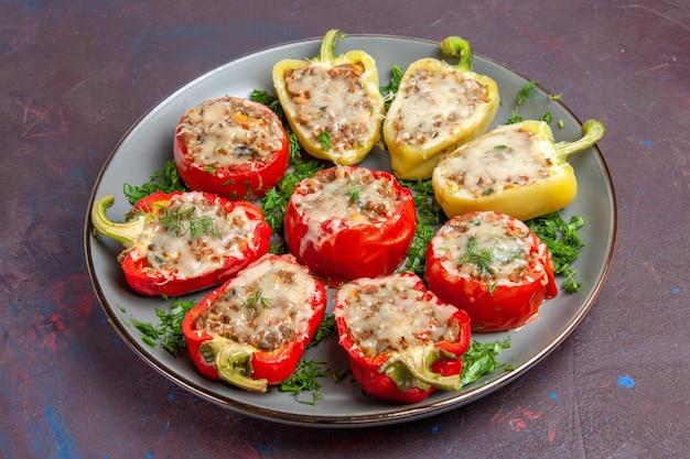 Vooraanzicht gebakken paprika met kaas greens en vlees binnen plaat op de donkere achtergrond bak diner schotel eten maaltijd