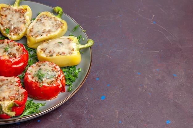 Vooraanzicht gebakken paprika's met kaasgroenten en vlees in plaat op donkere vloer bak diner schotel eten maaltijd