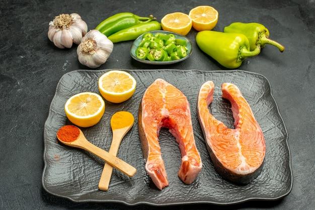 Vooraanzicht gebakken vleesplakken met pepers, knoflook en citroen op donkere achtergrondkleur maaltijdschotel ribsalade eten