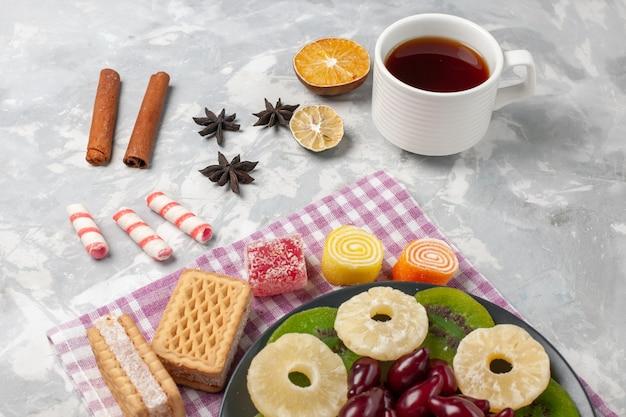 Vooraanzicht, gedroogd fruit, ananasringen, kornoeljes, wafels, thee en kiwiplakken op een witte ondergrond