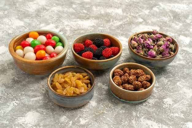 Vooraanzicht gedroogde bloemen met noten snoepjes en bessen confitures op witte achtergrond snoep koekje thee suiker koekje zoet